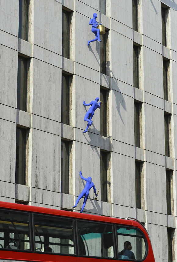 Sculptures entitled Blue Men are seen on the wall of a building on Borough High Street in south London.