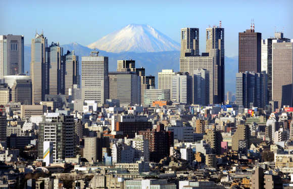 Mt Fuji looms over skyscrapers in Tokyo's Shinjuku district.