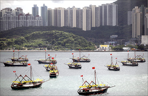 Fishing vessels bearing both Chinese and Hong Kong flags sail in Hong Kong's Victoria harbour.