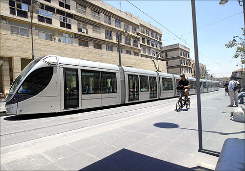 A man rides a bicycle next to a light rail tram in Jerusalem.