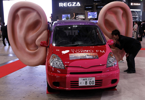 A man talks into a large model of a ear which has recording capabilities on a car.