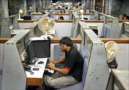 A stockbroker sits in his booth as he follows the latest share prices during a trading session inside the trading hall of the Karachi Stock Exchange.