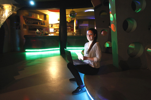Daria Vitasovic, a 27 year-old bar manager, poses for a picture as she works on her laptop in a night bar in Zagreb.