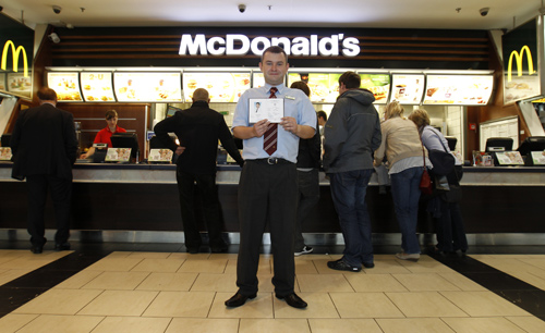 Marcin Lubowicki, a 28 year-old deputy manager of a McDonald's restaurant, poses with his university diploma in front of the fast food chain in the Arkadia shopping mall, Warsaw.
