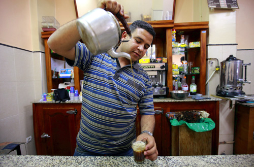 Sofiane Moussaoui, a 26 year-old waiter, poses for a picture as he serves tea for customers in a cafe in Algiers.