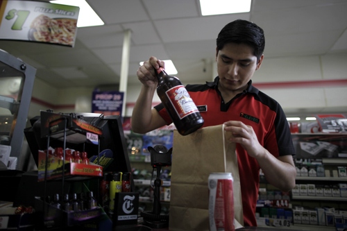 Abel Santiago, 21, serves a customer at a 7-Eleven convenience store in Santa Monica, California.