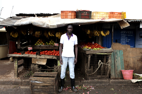Karl Moi Okoth, a 27 year-old vegetable and fruit seller, poses for a picture in front of his makeshift shop in Nairobi's Kibera slum in the Kenyan capital.