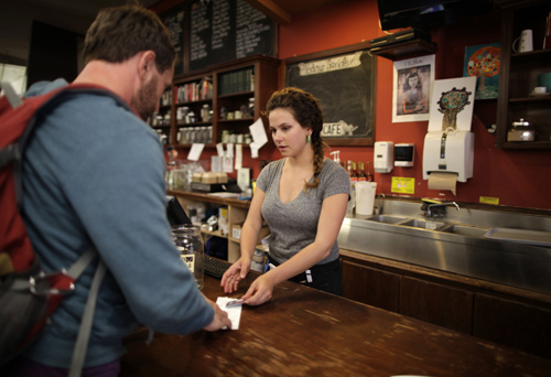 Jessica Mazza, a 28 year-old waitress, serves a customer at Novel cafe in Santa Monica, California.