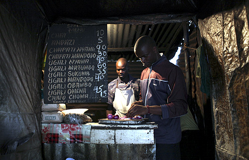 Denis Onyango Olang, (R), a 26 year-old assistant cook, prepares food in a dimly lit kitchen at a hotel in Nairobi's Kibera slum in the Kenyan capital.