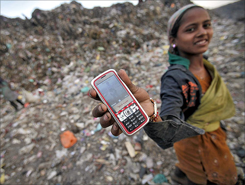 A ragpicker holds her mobile phone to show a picture she took at a dump yard on World Environment Day in New Delhi.