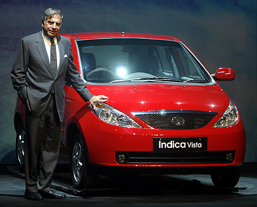 Tata Motors Chairman Ratan Tata poses with the company's new Indica Vista car during its launch in Mumbai.