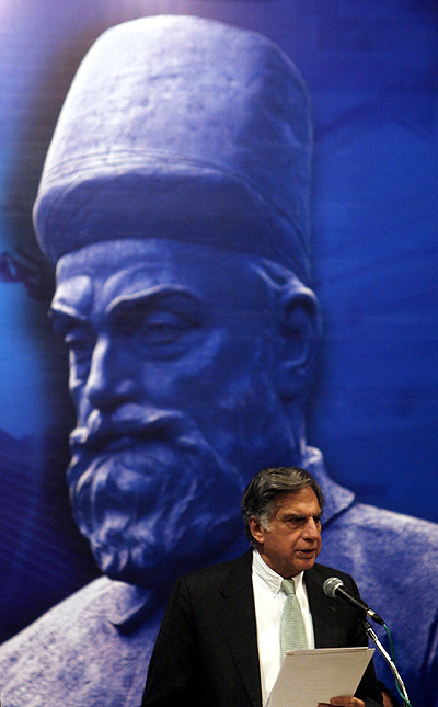 Chairman of Tata Group Ratan Tata speaks in front of a portrait of Tata Group founder Jamsetji Nusserwanji Tata.