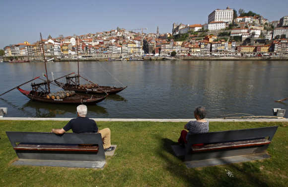 People enjoy the view along the Douro river in Porto, Portugal.