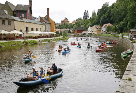People ride on their boats on Vltava river through the medieval city of Cesky Krumlov, 160km south from Prague, Czech Republic.