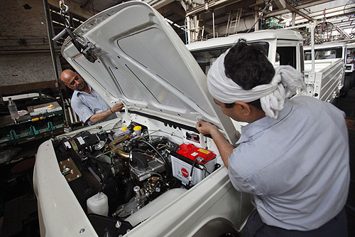 Employees affix a bonnet as they work on assembling a Mahindra Bolero vehicle at the company's manufacturing plant on the outskirts of Mumbai.