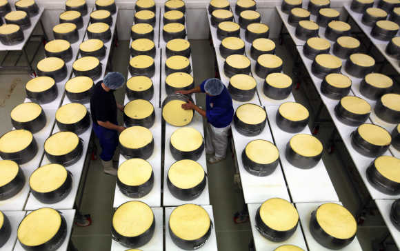 Employees work at a dairy plant in Litovel, one of the world's biggest producer of traditionally made parmesan cheese, in Italy.