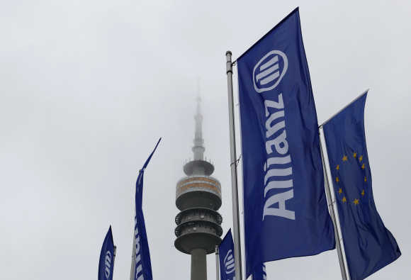 German insurer Allianz flags are seen in front of Munich's radio tower.