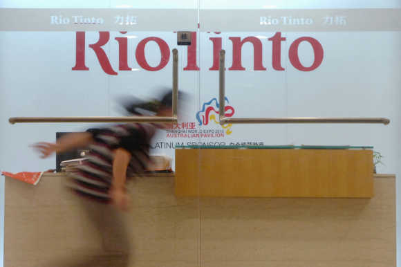 A woman runs past the reception desk of the Rio Tinto Limited Shanghai Representative Office in Shanghai.