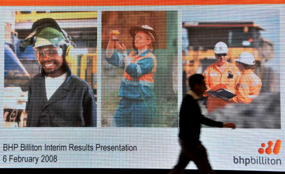 Man walks past screen displaying images for BHP Billiton interim results briefing in London.