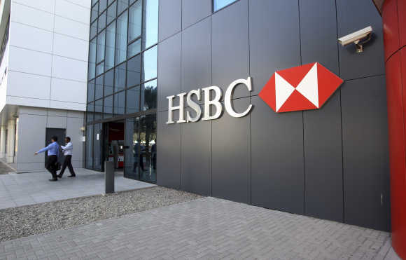 People exit an HSBC branch at Dubai Internet City in Dubai.