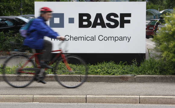 A cyclist rides his bike past the BASF plant in Schweizerhalle near Basel, Switzerland.
