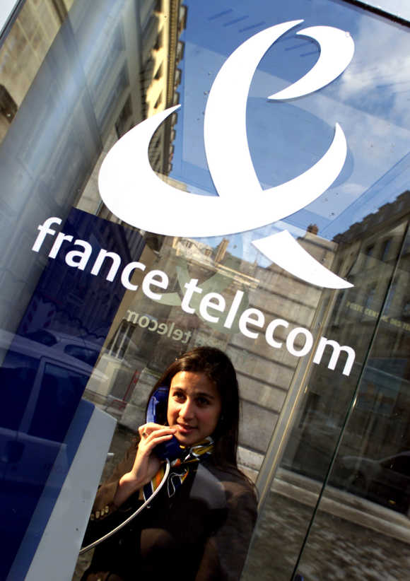 A woman makes a call in a booth in Paris, France.
