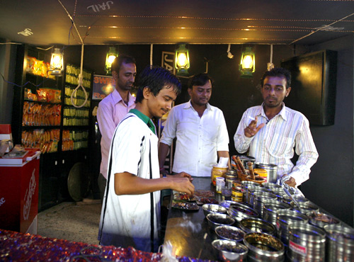 Ram Soni (2nd L) prepares paan.