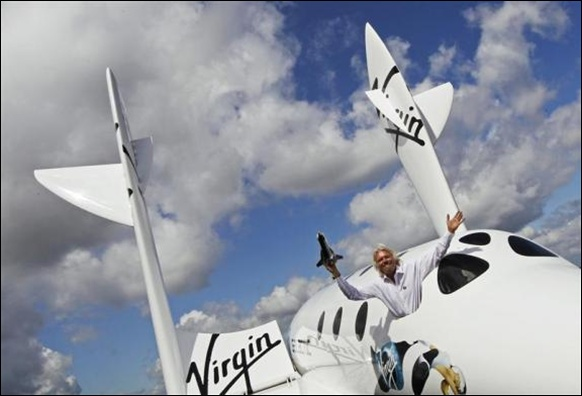 Entrepreneur Branson waves a model of LauncherOne cargo spacecraft from a window of an actual size model of SpaceShipTwo.