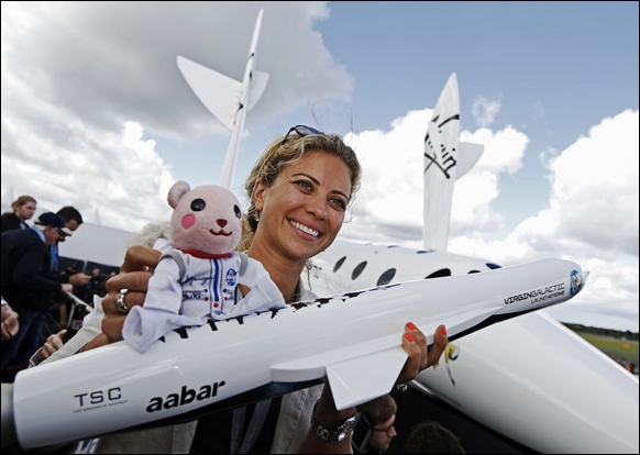 Branson's daughter, Holly, holds up a toy astronaut on top of a model of the LauncherOne cargo spacecraft.