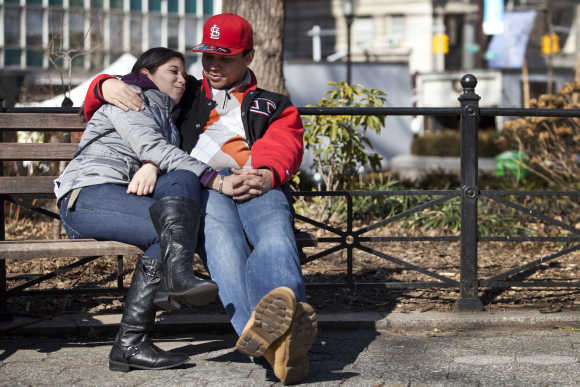 Two people cuddle on a bench in Union Square in New York.
