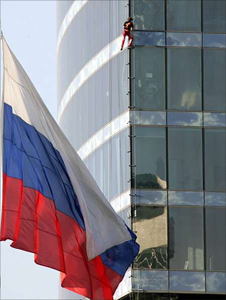 French extreme climber Alain Robert climbs the tower in Moscow as the Russian state flag is seen on the left.