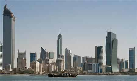 A fishing boat passes in front of the Kuwait City skyline