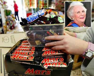 shopkeeper removes Mars Bars and Snickers Bars from the shelves of her convenience store (Inset: Jacqueline Mars)