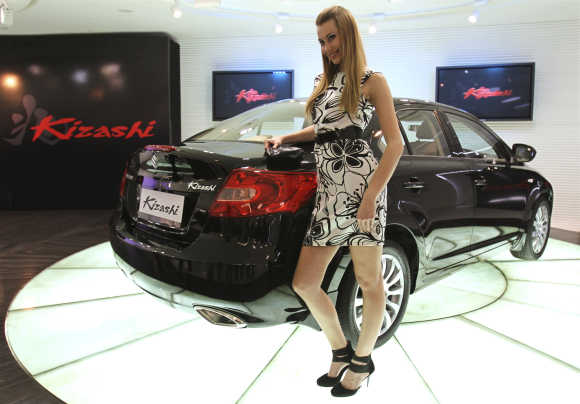 A model poses with 'Kizashi' car in New Delhi.