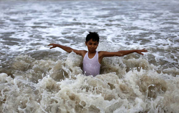 A boy plays in the waters of the Arabian Sea as it drizzles during a pre-monsoon shower in Mumbai.