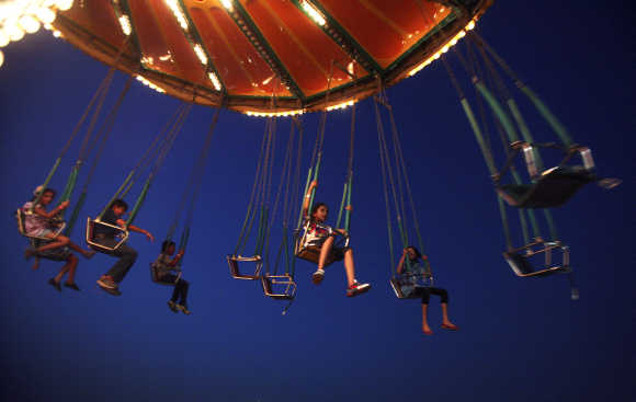 Children enjoy a ride at an amusement park in Noida.