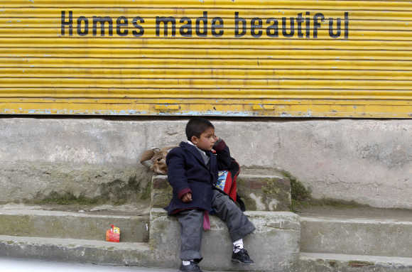 A Kashmiri school boy waits for a bus by a road side in Srinagar.
