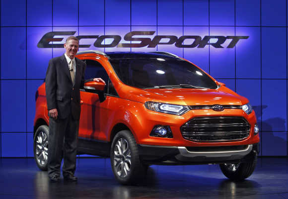 Alan Mulally, President and CEO of Ford Motor, poses next to EcoSport in New Delhi.