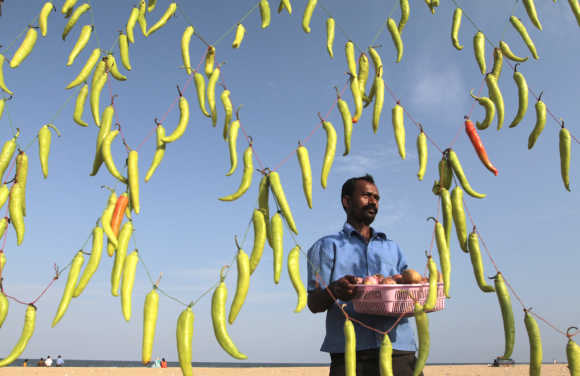 A vendor carries a basket containing onions and potatoes to prepare Chilli Bhaji, a local cuisine, at his stall decorated with green chillies to attract customers, in Chennai.