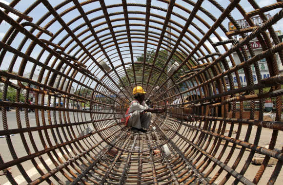 A worker tightens steel rebars at a construction site of a metro station in Chennai.