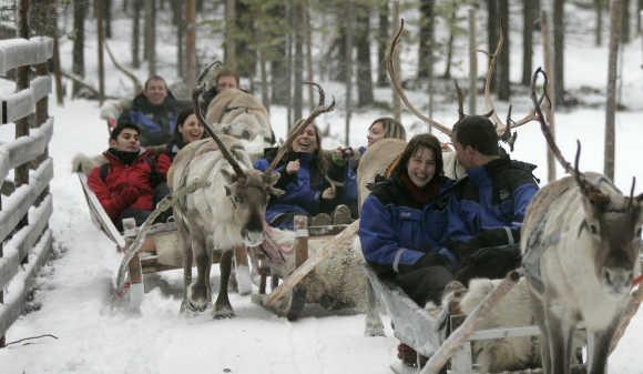 Tourists take part in the reindeer safari at Arctic Circle near Rovaniemi, Finland.