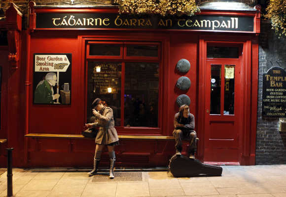 People hang around outside a bar in the Temple Bar area of central Dublin.