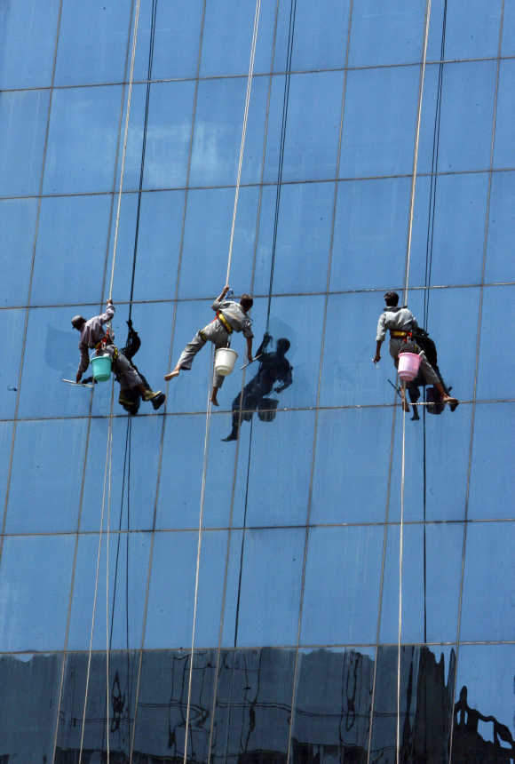 Window cleaners work on a high rising building in New Delhi.