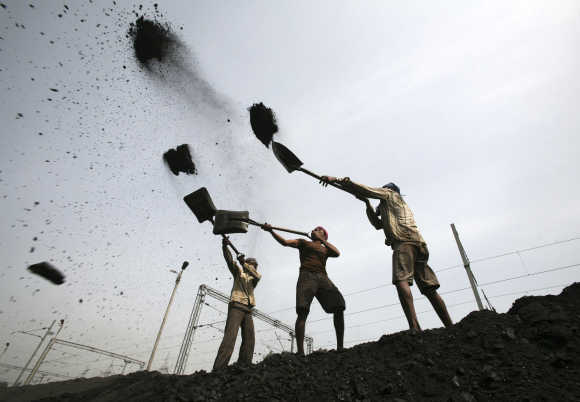 Labourers load coal on trucks at Bari Brahamina on the outskirts of Jammu.