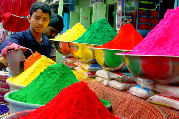 A vendor sells coloured powder on the eve of Holi in Bhopal.