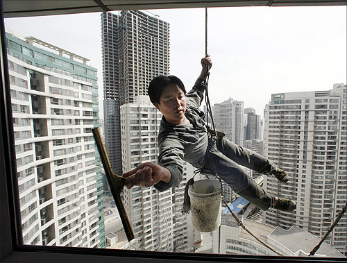 A worker cleans the windows of an apartment block in Beijing's central business district.