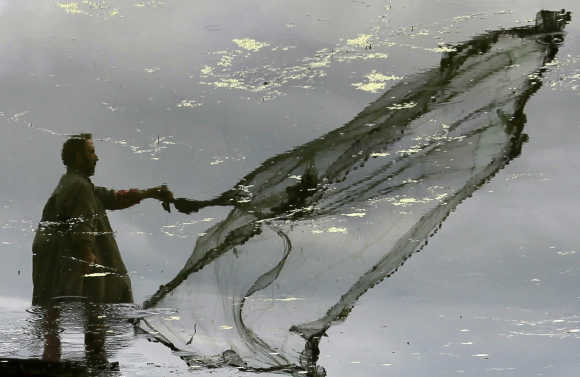 A Kashmiri fisherman is reflected in the waters of Dal Lake as he throws a net to catch fish in Srinagar.