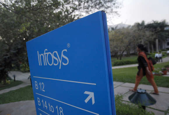 An employee walks past a signage board at the Infosys campus at the Electronics City IT district in Bengaluru.