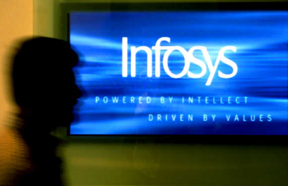 A man walks past a billboard of Infosys office in Bangalore.