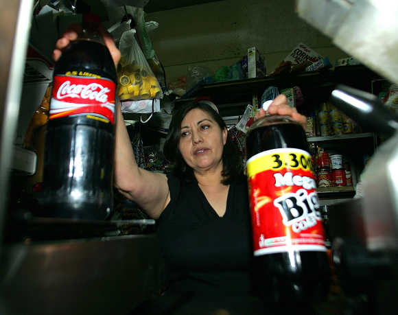 Raquel Chavez, 49, owner of the La Racha's store shows a Coca-Cola bottle and a Big Cola bottle in Mexico City.